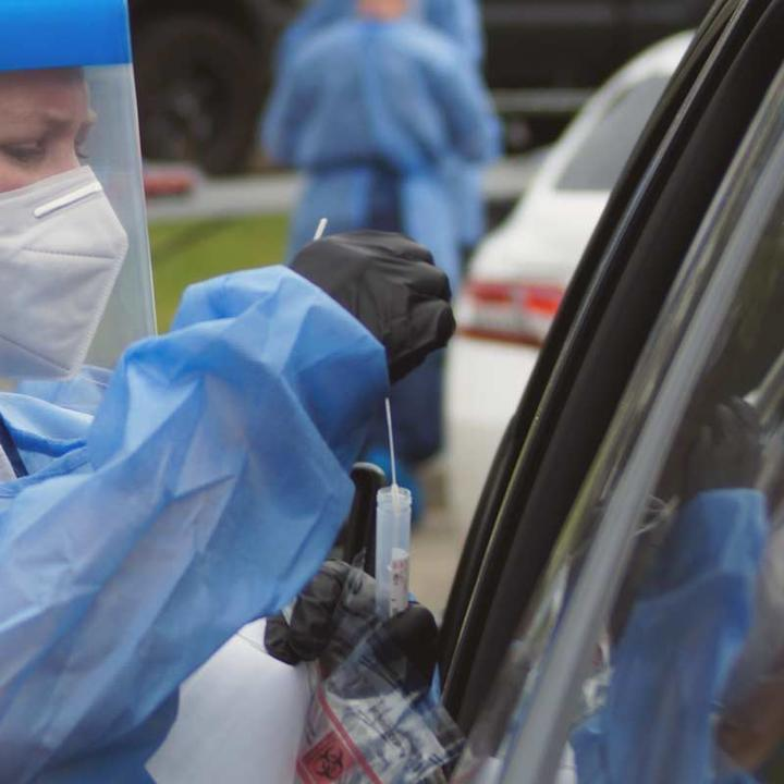 A nurse performing a nasal swab test through a car window.