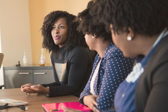 Three women meeting at a conference table.